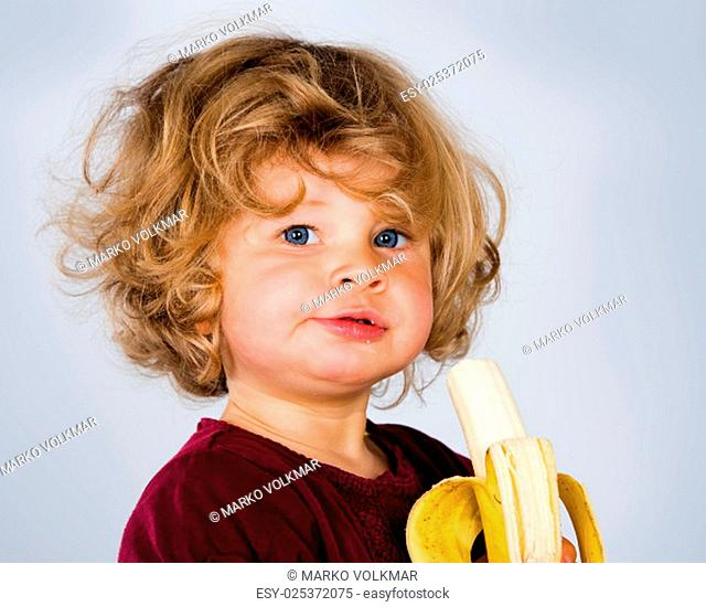 little girl is eating banana and looking in to the camera