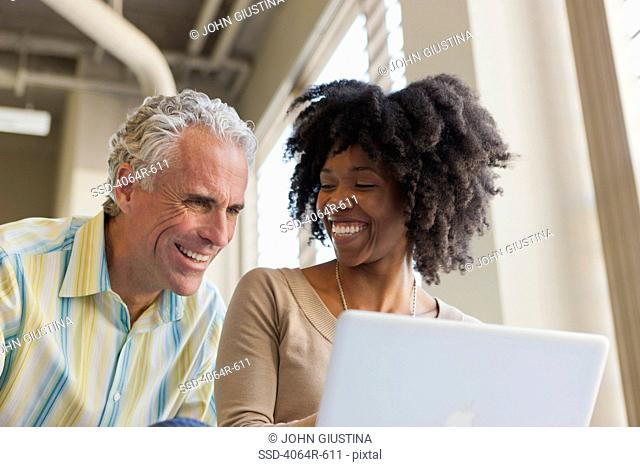 Businessman and woman using laptop in office