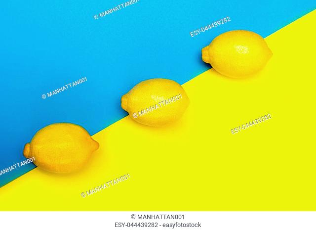 Three yellow lemons in a row on a yellow-blue background