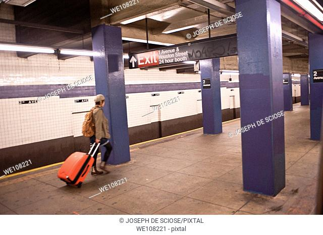 A lone traveler pulls an orange suitcase on an empty subway platform in New York City