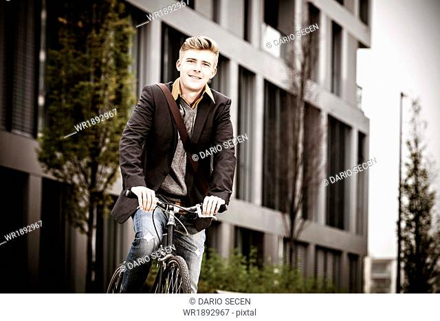 Young businessman with bicycle, Munich, Bavaria, Germany