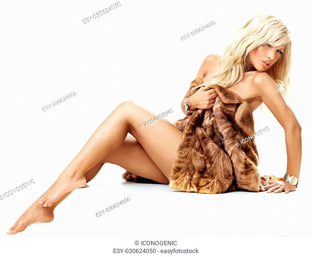 Young tanned blond woman with bare legs wrapped in mink coat