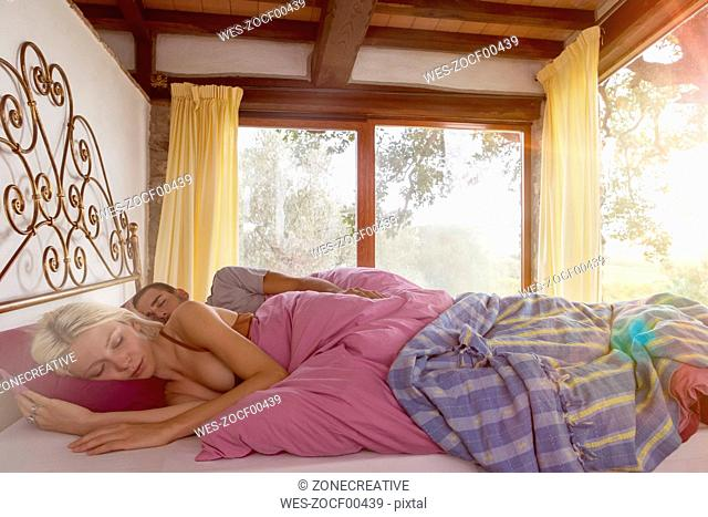 Young romantic couple waking up in bed
