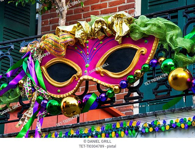 Mardi Gras mask hanging on balcony's railing