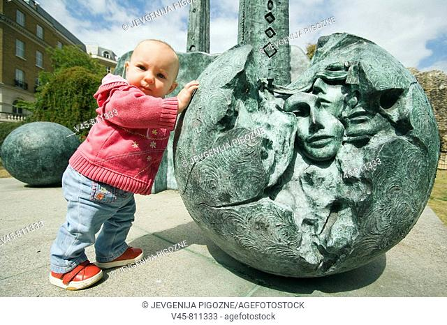 Baby girl pushing a ball of the contemporary sculpture near Reading Abbey Berkshire, England