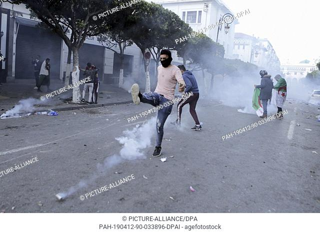 12 April 2019, Algeria, Algiers: An Algerian protester kicks back a tear gas canister fired by Algerian security forces during clashes that followed an...