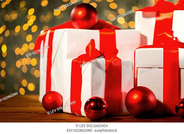 christmas, holidays, presents, new year and celebration concept - close up of gift boxes and red balls on wooden floor over lights background