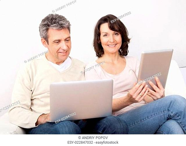 Mature couple using laptops in couch