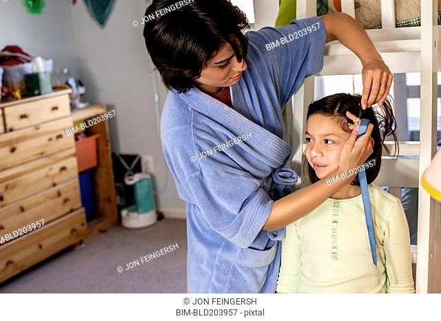 Hispanic mother brushing daughter's hair