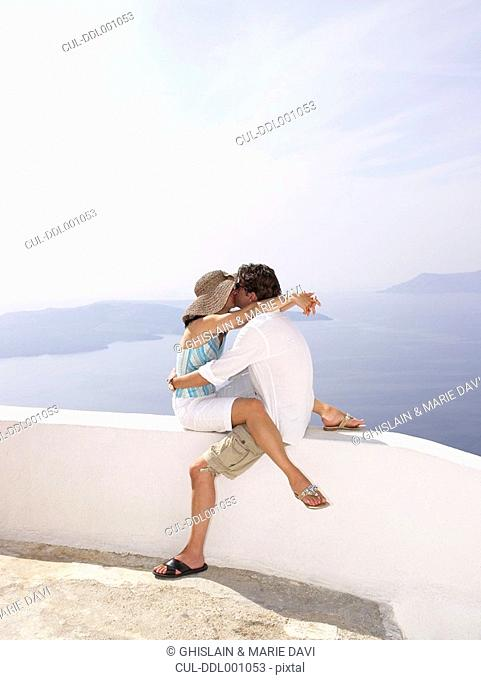 Couple kissing on a low wall, sea view