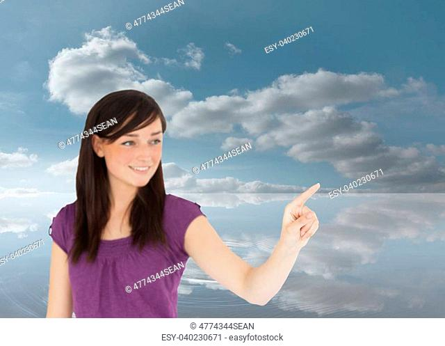 Composite image of attractive brunette pointing something with her finger in the cloudy sky