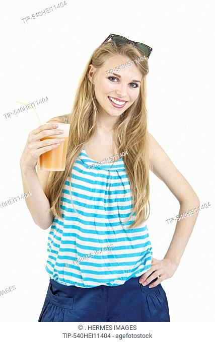 Happy young woman enjoying a glass of cold drink