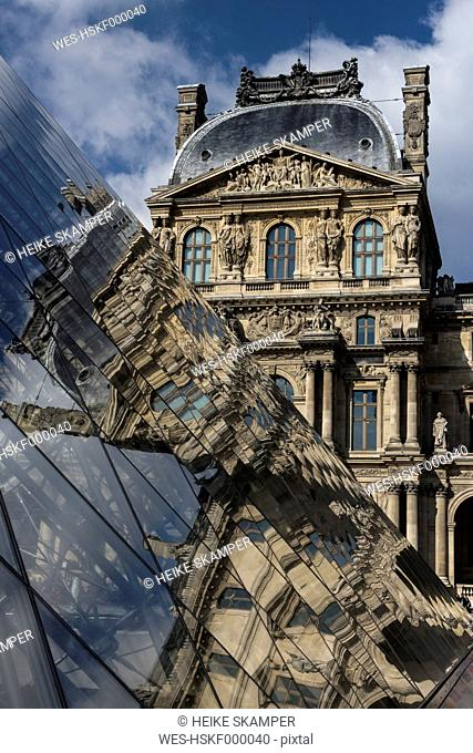 France, Paris, Louvre, view to facade with reflection on glass pyramide in the foreground