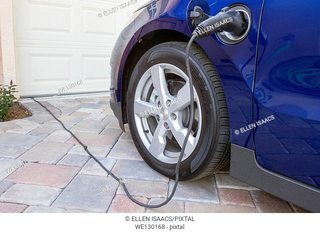 Plug-in electric car with connector plugged in charging, at home in a driveway