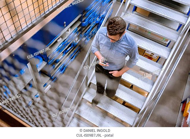 High angle view of manager looking at smartphone on stairway in factory