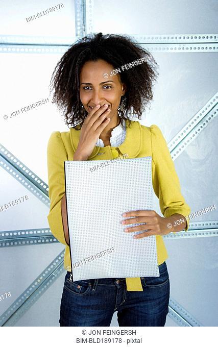 Surprised Ethiopian businesswoman holding envelope