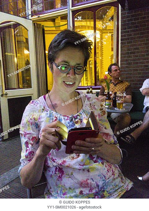 Tilburg, Netherlands. Mature adult woman checking her smartphone messages while enjoying an evening at a cafe's terrace