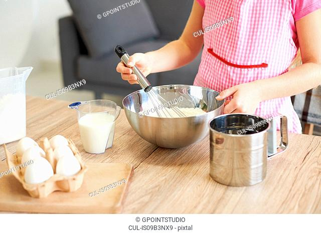 Young girl whisking ingredients together in bowl, mid section