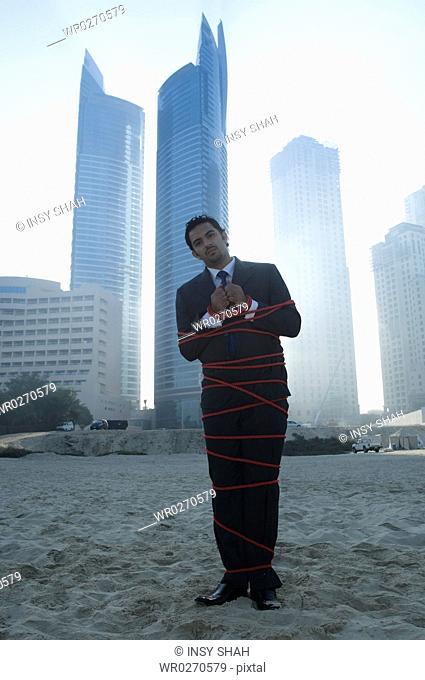 Businessman tied with rope, towers seen through the mist in the background