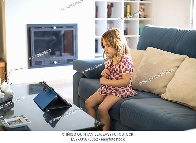 blonde four years old girl sitting in blue sofa indoor house watching very concentrated a digital tablet on the table