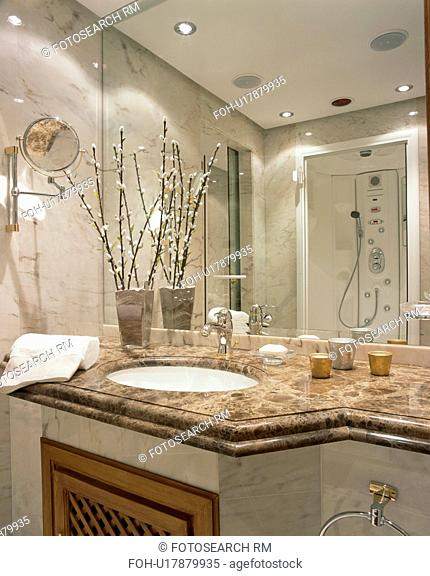 Mirrored wall above underset basins in green marble vanity unit