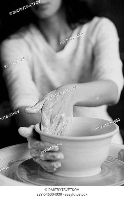 Young beautiful pretty woman with brunette dark hair working on pottery wheel and sculpting clay pot. Shallow DOF. Focus on hands