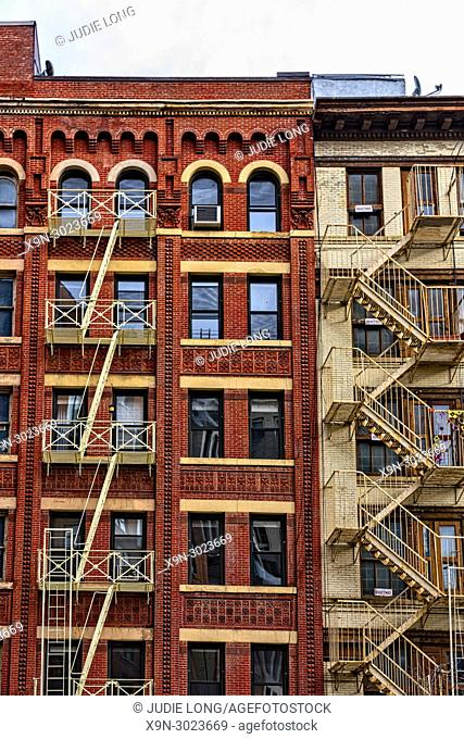New York City, Manhattan, Tribeca. Looking up at Two Cast Iron Buildings with Fire Escapes and Arched Windows
