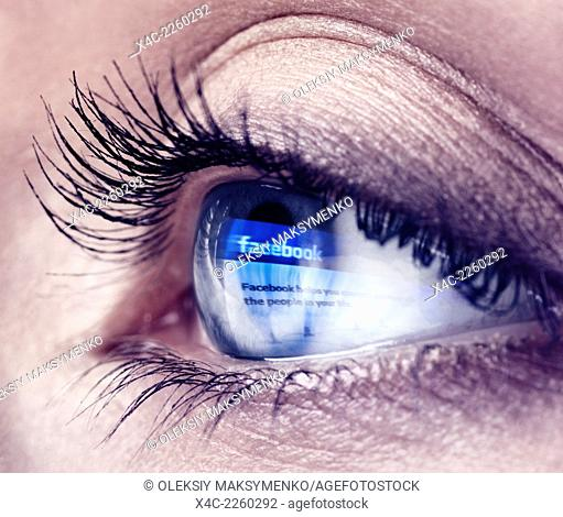 Closeup of a young woman blue eye with Facebook logo reflecting in it