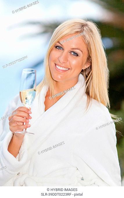 Woman in bathrobe drinking champagne