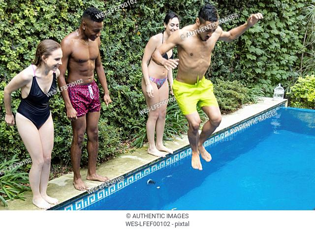 Happy friends jumping into swimming pool