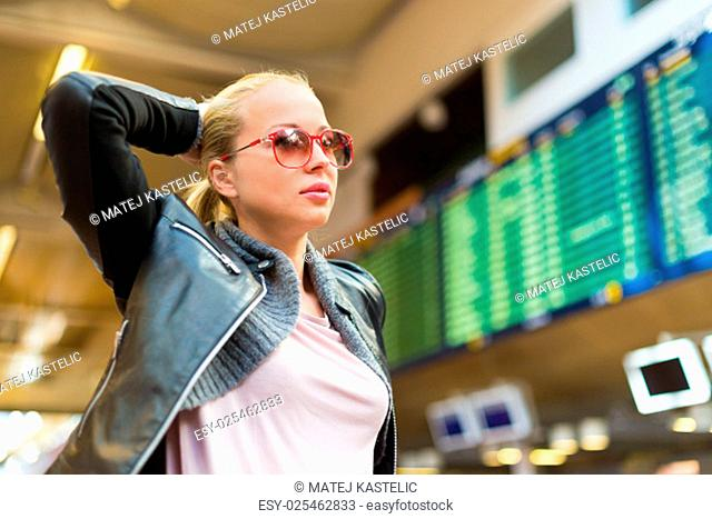 Casually dressed young stylish female traveller checking a departures board at the airport terminal hall in front of check in couters