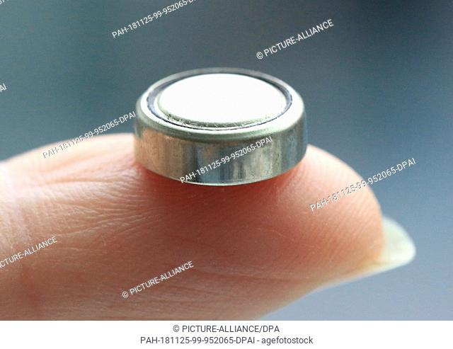 "25 November 2018, Berlin: ILLUSTRATION - A so-called """"button cell"""" is held on a finger. If small children swallow them"