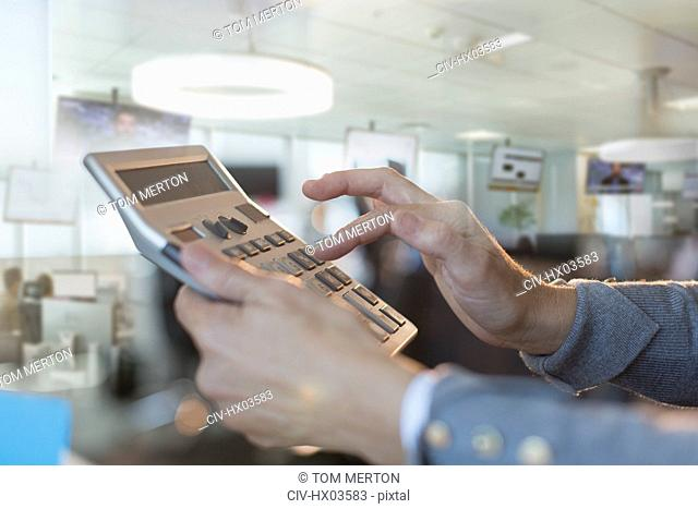 Close up businessman using large calculator in office