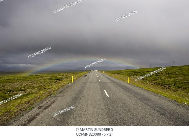 Rainbow stretching over rural road, Iceland