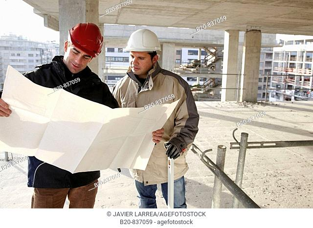 Architect and construction worker looking at blueprints, personal protective equipment, housing construction, concrete skeleton