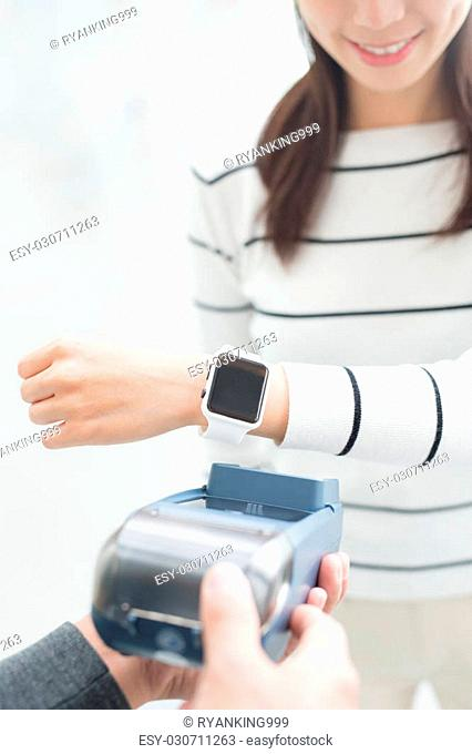 young woman pay by smart watch with empty screen, great for your design,asian beauty