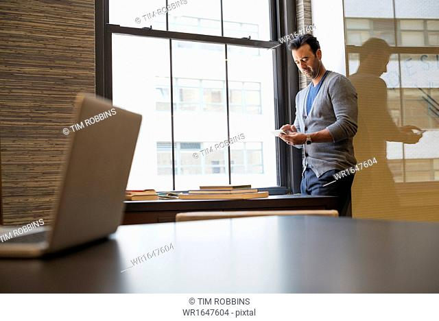Office life. A man standing by a window in an office checking his smart phone