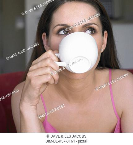 Woman drinking from teacup, Perth, Australia