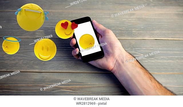 Digital composite image of hand holding smart phone while emojis coming out of it