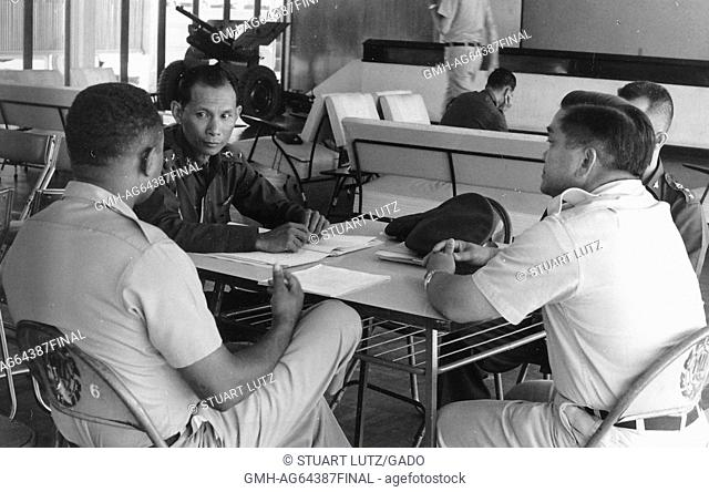Lieutenant AL Walker sitting at a table, indoors, talking to two Vietnamese soldiers, Vietnam, 1964