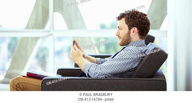 Businessman using cell phone in lobby