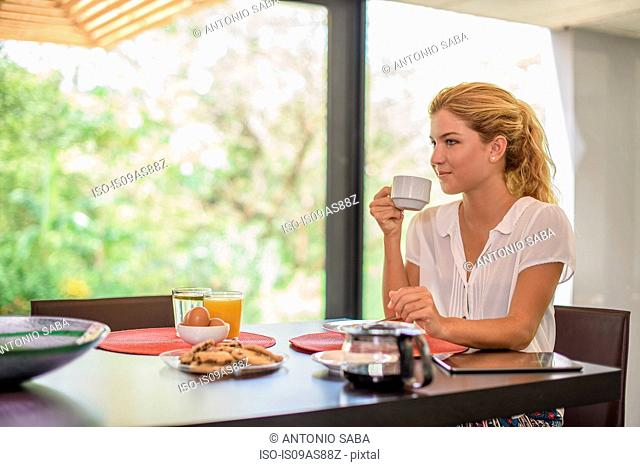 Young woman at breakfast table drinking coffee