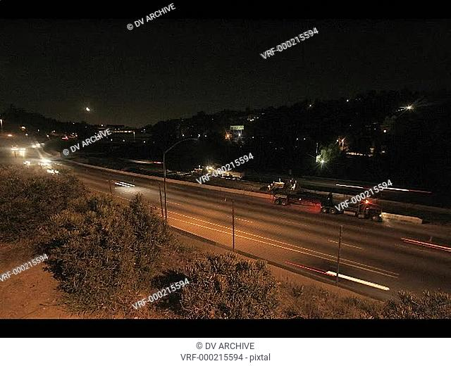A time-lapse view of a highway at night near a city