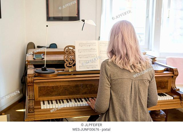 Back view of woman playing piano at home