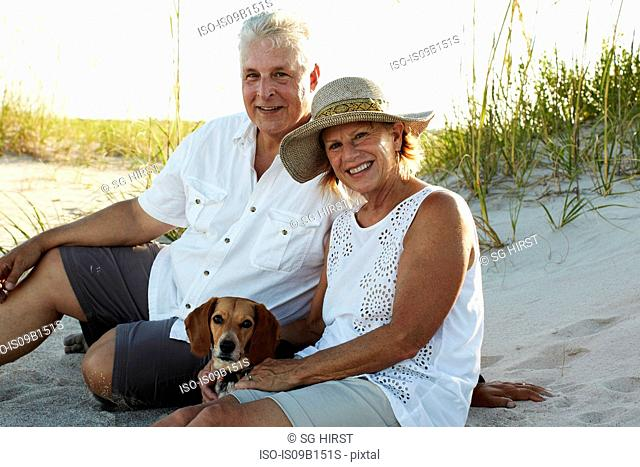 Portrait of senior couple sitting on beach with pet dog