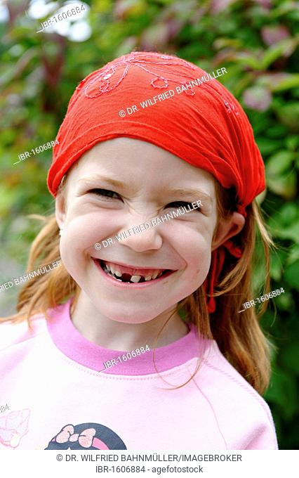 Girl with fallen out tooth and loose tooth