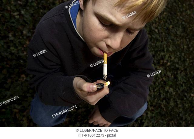 Boy lighting a cigarette