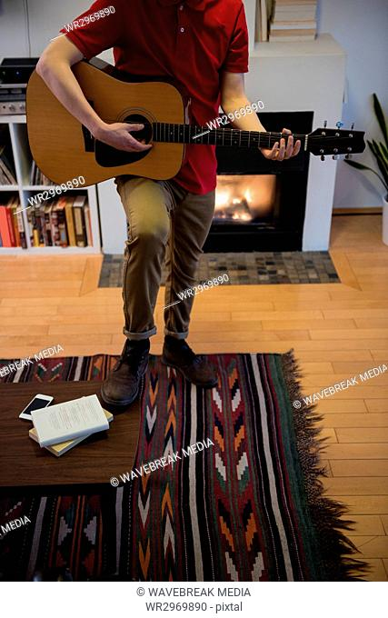 Man playing guitar in living room