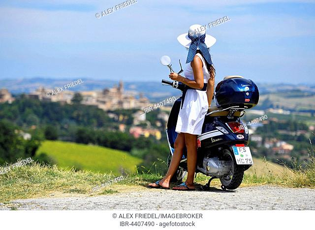 Woman with white sunhat next to Vespa Primavera scooter, Corinaldo, Marche, Italy