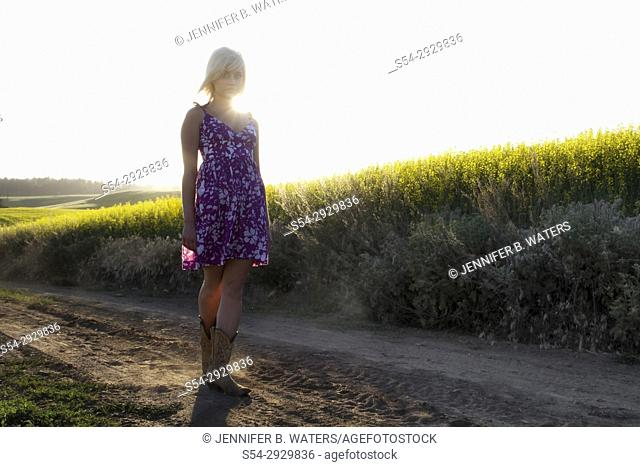A young woman on a rural road by a canola field, Spokane County, Washington, USA